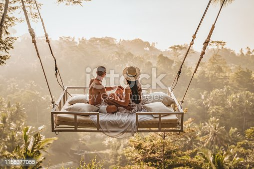 Photo of the couple in love. The morning in a bed filled with tenderness and romance. happy man and a woman sitting on flying bed over the tropical Forrest. Bali, Indonesia. Successful couple relaxing at a luxury villa with a beautiful view at the rice terraces,  honeymoon at Bali, Ubud.