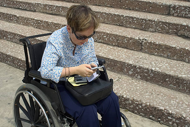 inaccessible building, accessible technology woman in frotn of inaccessible building access making a call with her mobile phone discriminatory stock pictures, royalty-free photos & images