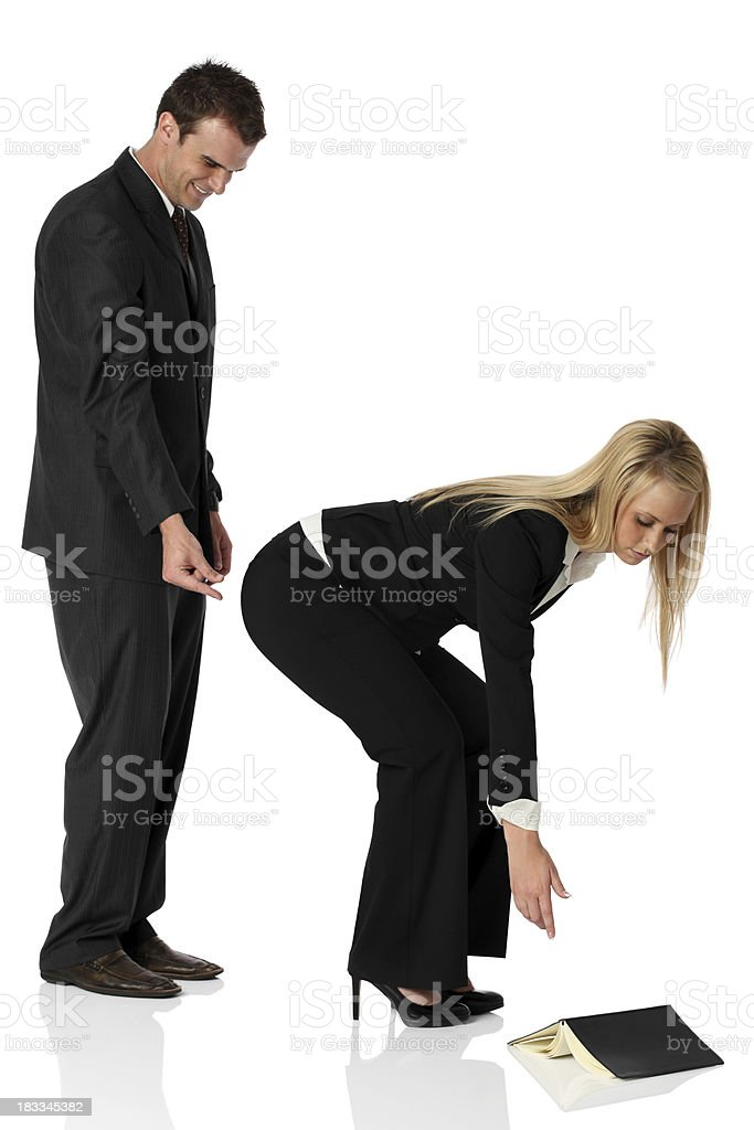 Inappropriate businessman reaching to pinch businesswoman's behind stock photo
