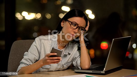 593328060 istock photo Inattentive young woman chatting smartphone, avoiding work, job indifference 1144431504