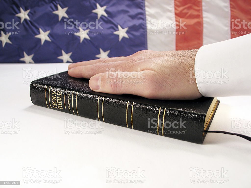 Inauguration Concept: Hand on Bible with American Flag Background stock photo