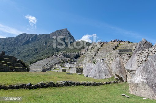 Tourists visting Machu Picchu, the citadel of the Inca Empire located in Peru, South America, during a hot summer morning.