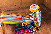 Inca woman weaving alpaca wool