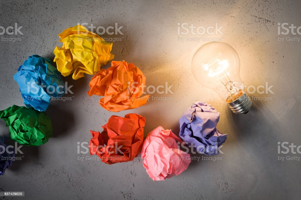 Incandescent bulb and colorful notes on concrete background stock photo