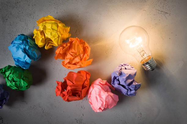 Ampoule à incandescence et des notes colorées sur fond de béton - Photo