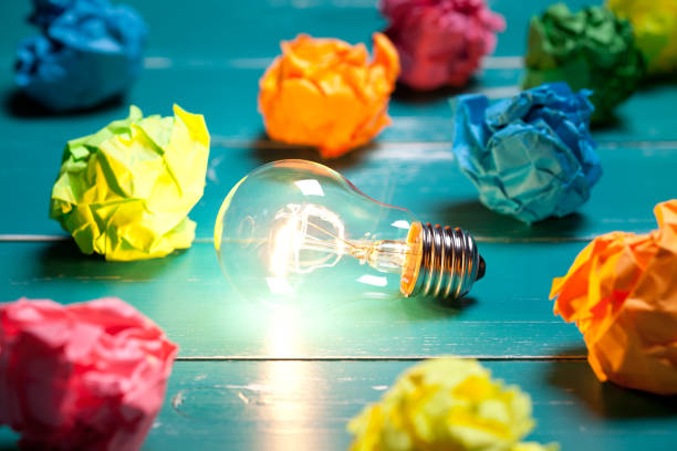 incandescent bulb and colorful notes on turquoise wooden table - creativity stock photos and pictures