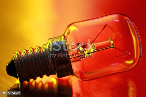 Incandescent Light Bulb in abstract color illuminated.