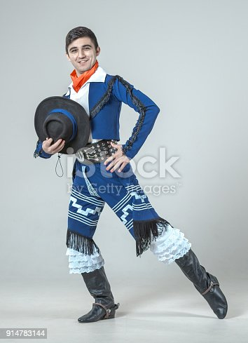 The young man dressed in the traditional gaucho costume (Latin-America). The man is dancing the folk dance. He is holding his hat in hand. The dancer is smiling looking at the camera. Studio shooting on white background