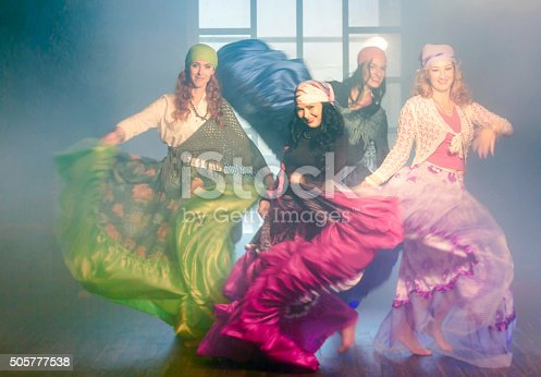 Four women dressed in gypsy clothes are dancing barefoot on wooden floor. The cute women Gypsies are waving their long skirts on the background of big window