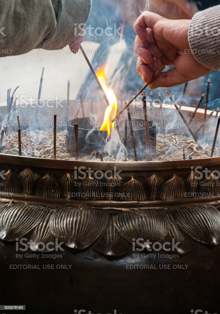 Incense being lit at a Buddhist temple foto de stock royalty-free