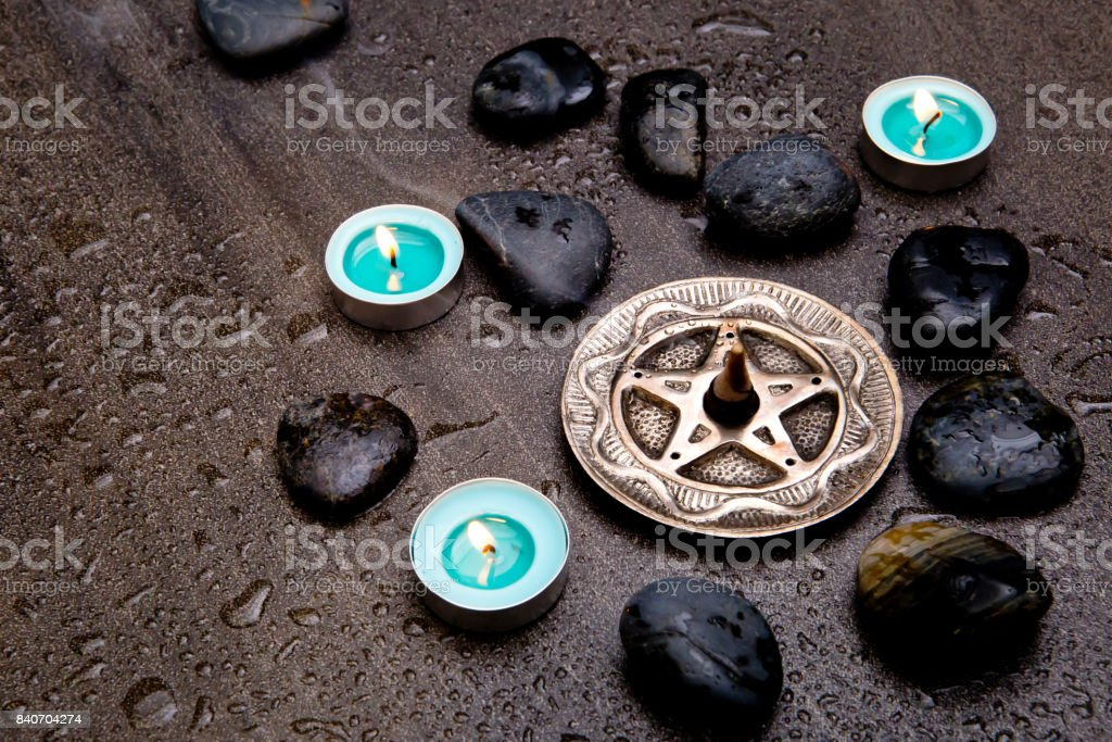 Incense burning in silver pentagram with blue candles and black rocks on gray slate stone background stock photo