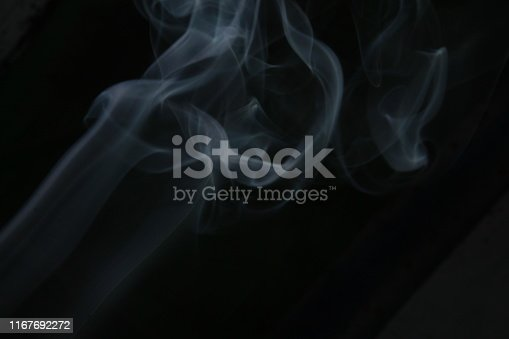 istock Incense stick and swirling smoke from incense burning. Beautiful smoke. Abstract close up background. Blurred background and design with copy space 1167692272