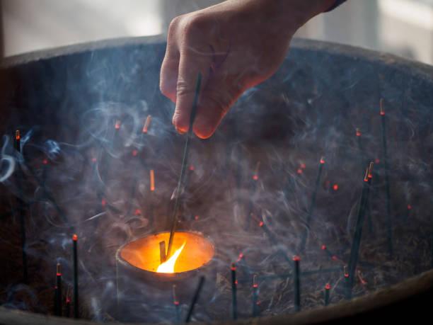 Incense stick lit by flame through smoke, Japan stock photo