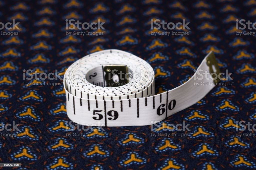 inch, centimeter tape on a background of blue fabric with a pattern stock photo