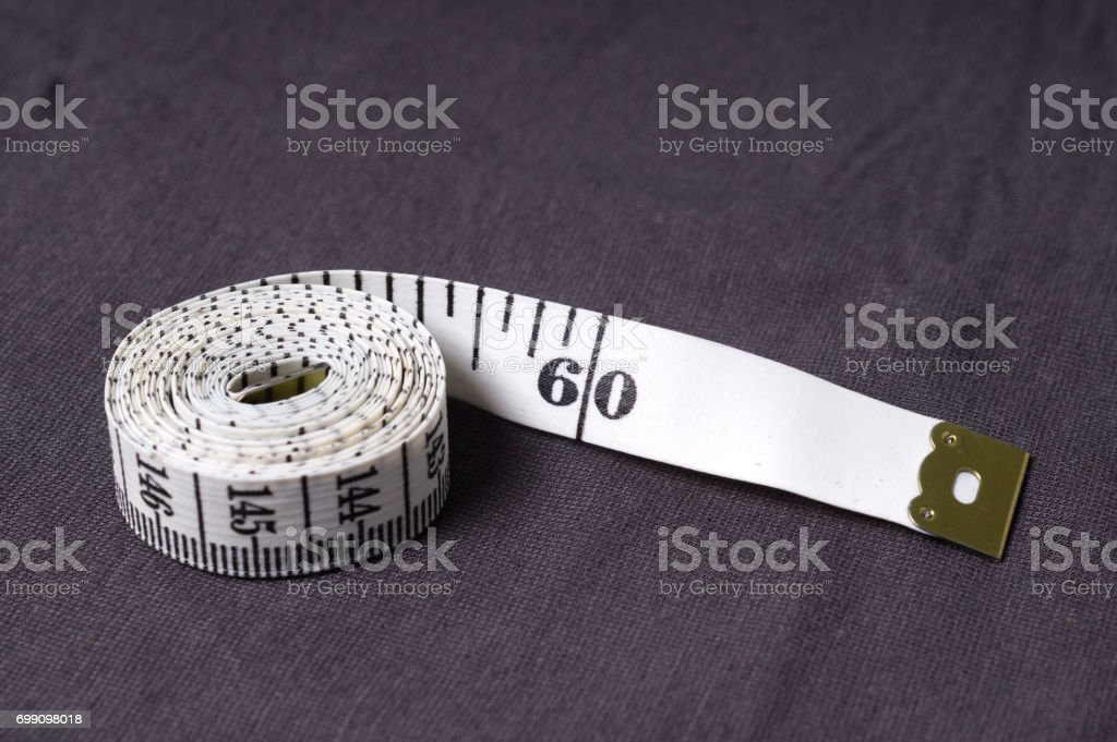 inch, centimeter tape on a background of grey fabric stock photo