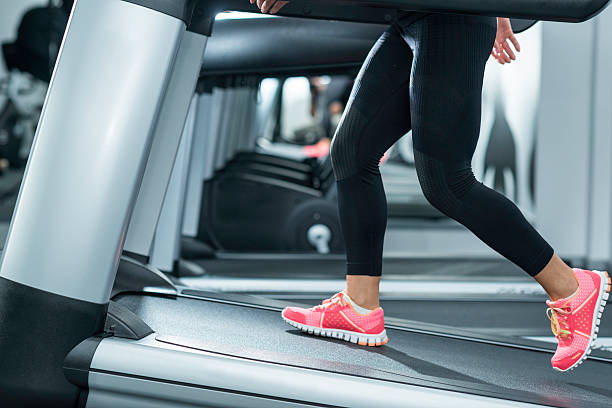 Incline Treadmill Running Woman using incline threadmill in modern gym. Incline threadmills are used to simulate uphill walking or running and deliver additional workout benefits to users. Woman is wearing black yoga pants andrunning sports shoes. steep stock pictures, royalty-free photos & images