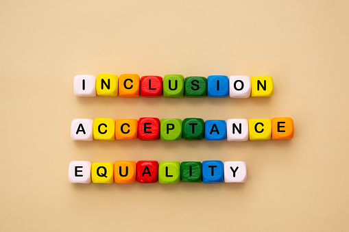 Inclusion, acceptance and equality words made from colorful wooden cubes. Inclusive and tolerance social concept.