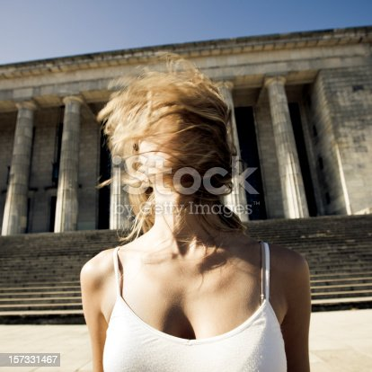 beautiful young woman in front of university of buenos aires, argentina with motion-blured twirled blonde hair. concept art portrait.
