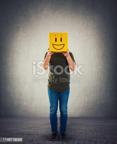 istock Incognito person holding a yellow box instead head. Introvert anonymous hiding face behind mask 1149718059