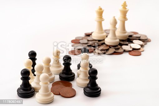 Income inequality and social issue concept theme with large group of chess pawns representing the poor and the middle class splitting a significantly smaller amount of money that a small group of rich