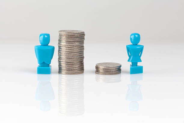 income inequality concept with figurines and coins - imbalance stock photos and pictures