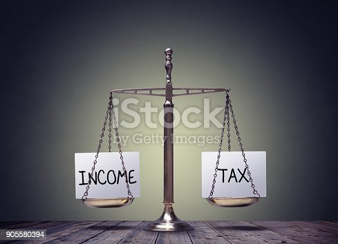 1018458132istockphoto Income tax balancing finance books scales concept 905580394