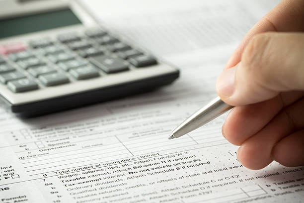 Income tax filling US individual income tax return form with pen and calculator 1040 tax form stock pictures, royalty-free photos & images