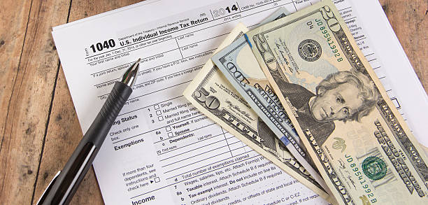 Income tax form 1040 with calculator and dollar bills stock photo