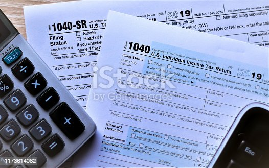 Forms 1040 and new Form 1040 SR for seniors on desktop with escape key showing from keyboard and tax key on calculator. Concept is escaping from deciding which form to use.