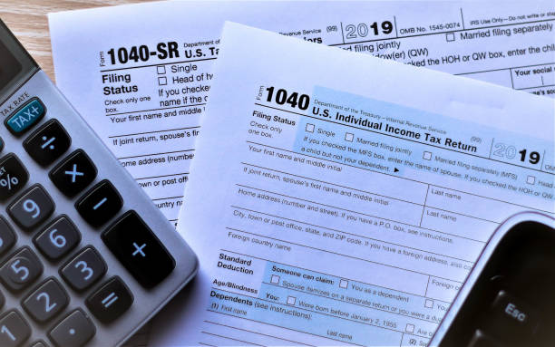 US Income tax forms 1040 and new 1040 SR for 2019 Forms 1040 and new Form 1040 SR for seniors on desktop with escape key showing from keyboard and tax key on calculator. Concept is escaping from deciding which form to use. taxes stock pictures, royalty-free photos & images