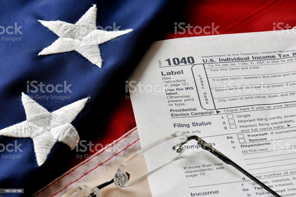 A 1040 Income tax paper with glasses and a US Flag royalty-free stock photo
