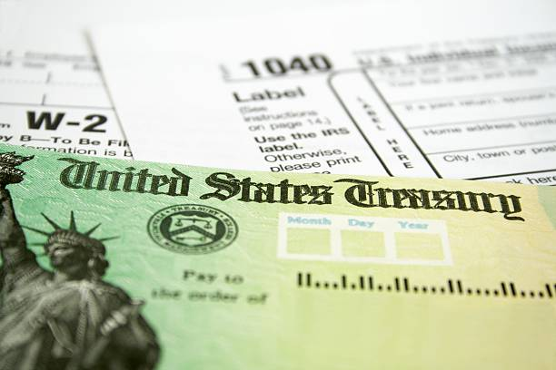 Income tax refund check on tax forms Tax Refund Check with W-2 and 1040 U.S. Individual Income Tax Return Forms refund stock pictures, royalty-free photos & images