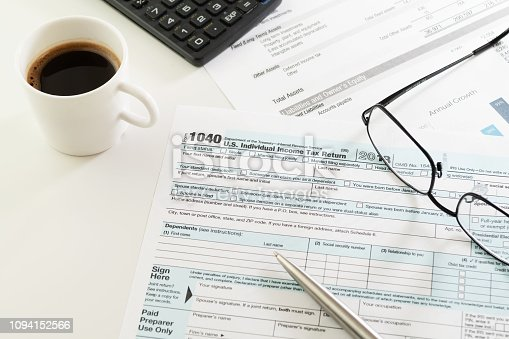 istock Income tax return form, cup of coffee, pen, calculator and glasses 1094152566