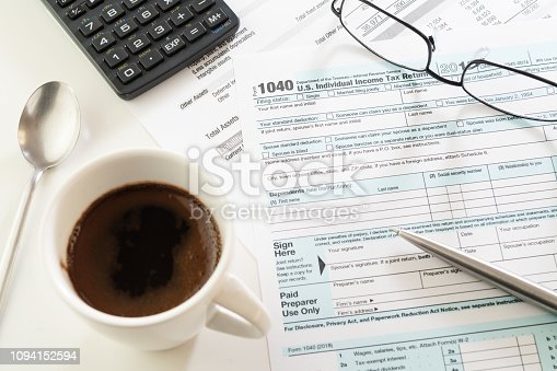istock U.S. income tax return form, cup of coffee, pen, calculator and glasses 1094152594
