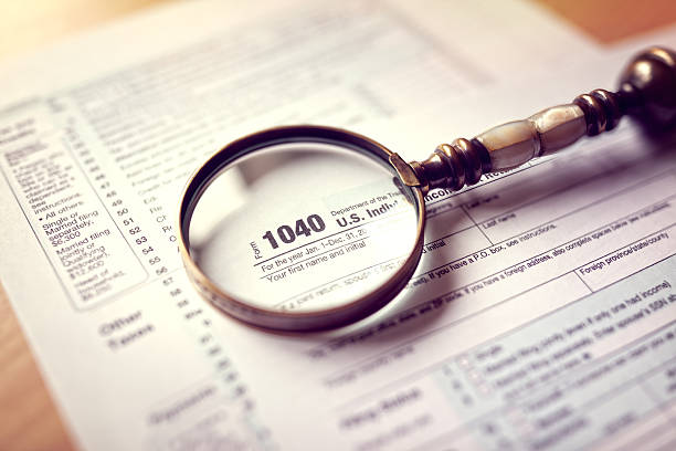 Income tax return form Income tax 1040 us individual tax return form and magnifying glass 1040 tax form stock pictures, royalty-free photos & images