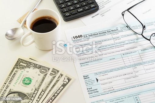 istock Income tax return form with a cup of black coffee, money and glasses on table 1094152688