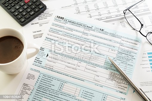 istock Income tax return form with espresso cup, calculator, glasses and pen on table 1094152530