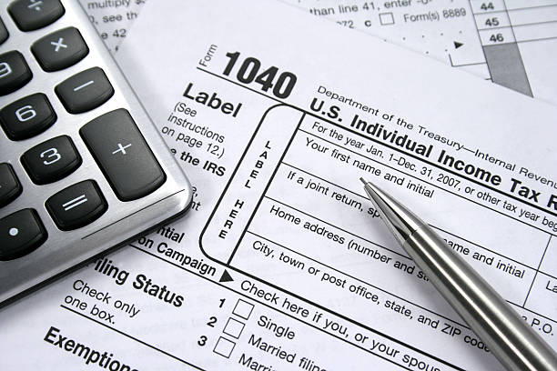 Income Taxes A 1040 Individual tax form with calculator and pencil. 1040 tax form stock pictures, royalty-free photos & images