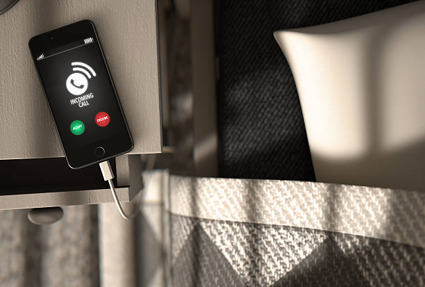 Incoming Call Cellphone Next To Bed stock photo
