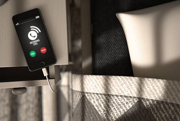 incoming call cellphone next to bed - nachttischleuchte stock-fotos und bilder