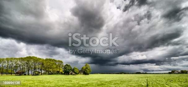 Approaching summer storm over meadows with a farm in the foreground. High dynamic range (HDR) effect.