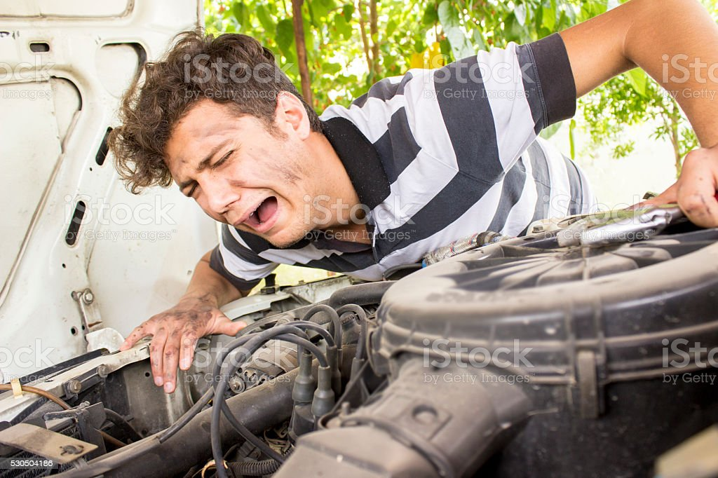Incompetent repairman crying next to car stock photo
