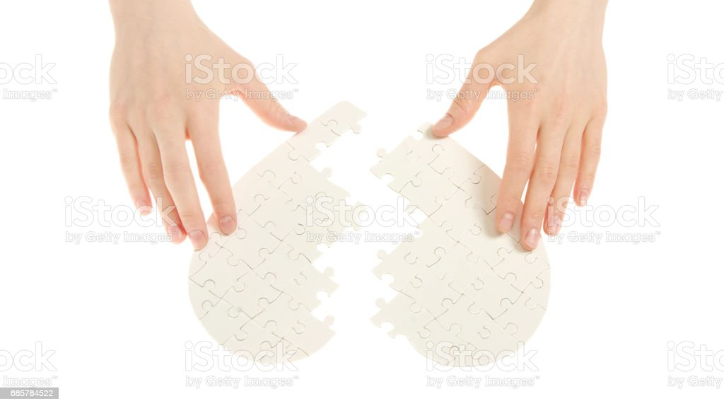 Incomplete jigsaw puzzle in a shape of a heart isolated on white royalty-free stock photo
