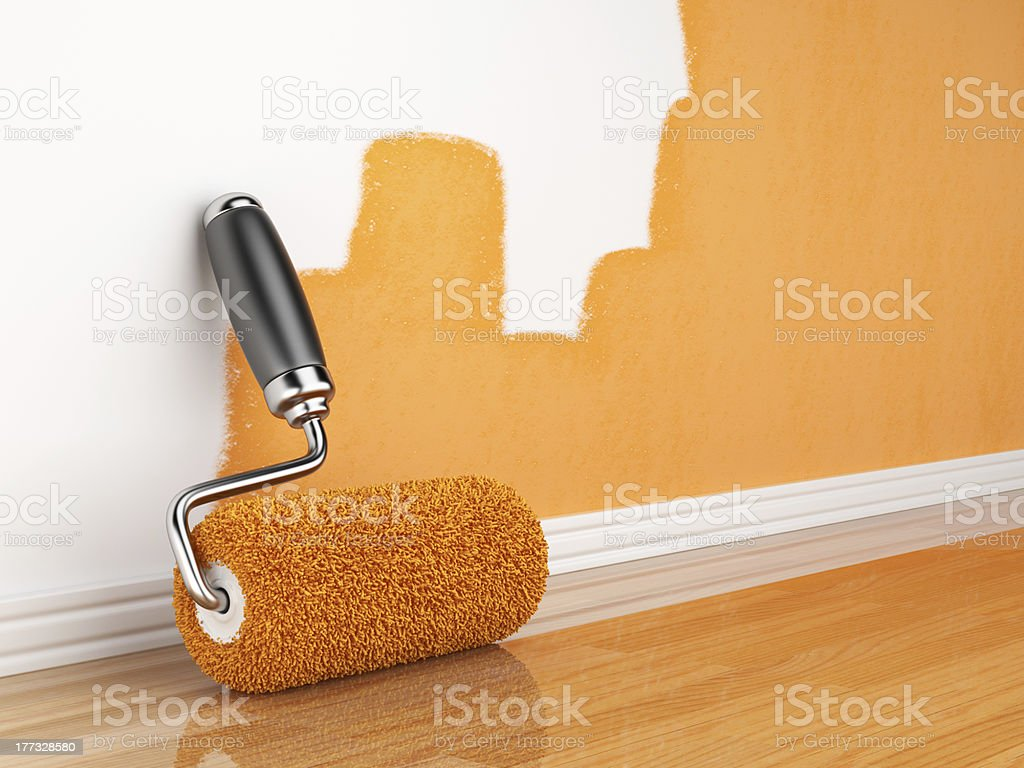 Incomplete orange wall painting with roller leaning on wall stock photo