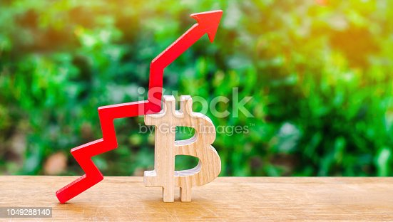 istock increase in the cost of bitcoin. growth of the crypto-currency market. blockchain technology. wooden sign bitcoin and red arrow up 1049288140