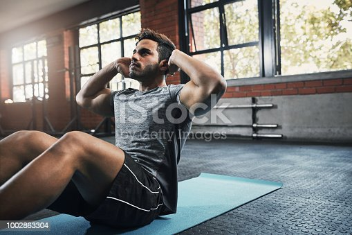 Shot of a handsome young man working out at the gym
