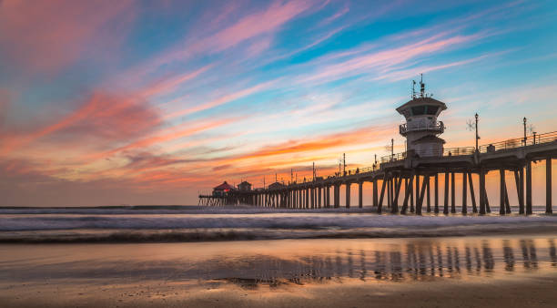 Incredible colors of sunset by Huntington Beach Pier, in the famous surf city in California stock photo