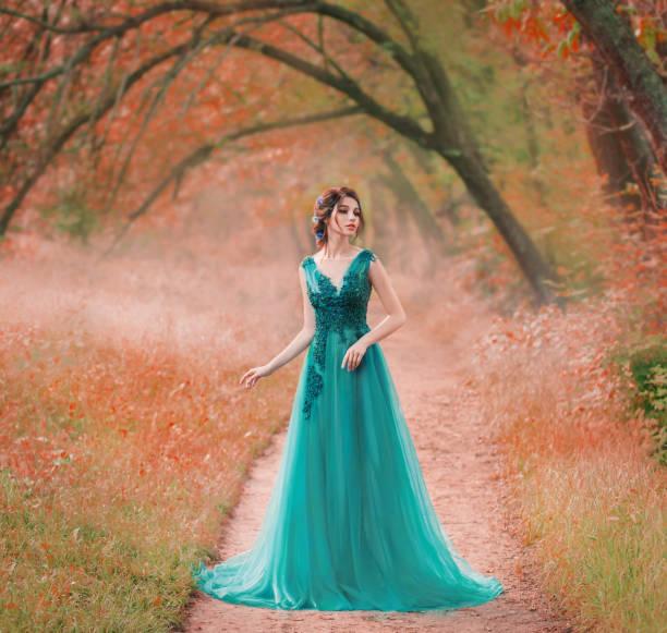 unglaublich niedliche meeresprinzessin spaziert allein durch einen roten märchenwald, eine magische fee in einem grünen türkisfarbenen kleid, eine niedliche dunkelhaarige nymphe wie eine magische blume, eine dame auf einem geheimen pfad, kreative farben - grüne wald hochzeiten stock-fotos und bilder