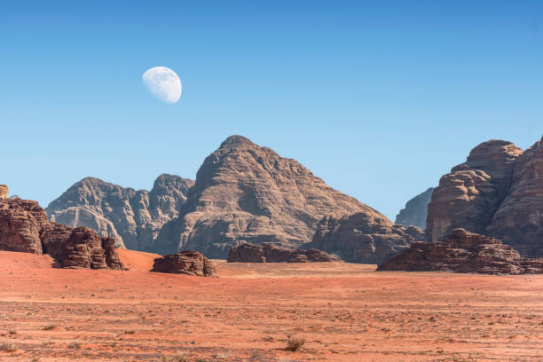 incredible lunar landscape with huge moon in Wadi Rum village in the Jordanian red sand desert. Wadi Rum also known as The Valley of the Moon,  Jordan - Image stock photo