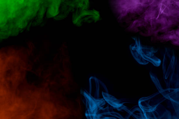 incredible multi-colored patterns of cigarette vapor mystical clouds along the edges of the frame on a dark background stock photo